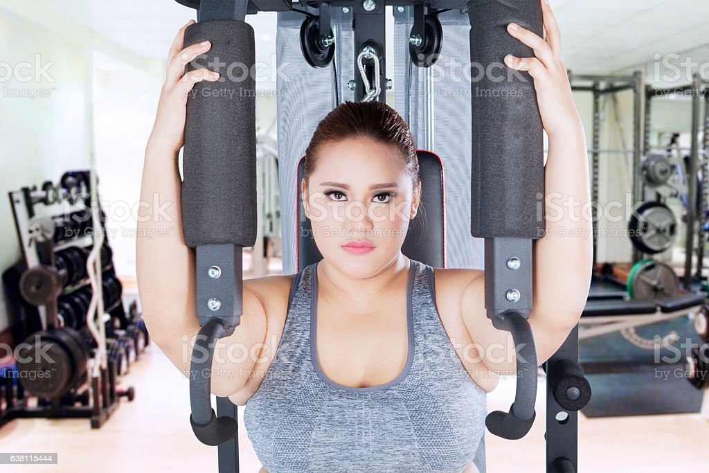 Strong overweight woman with shoulder press machine stock photo