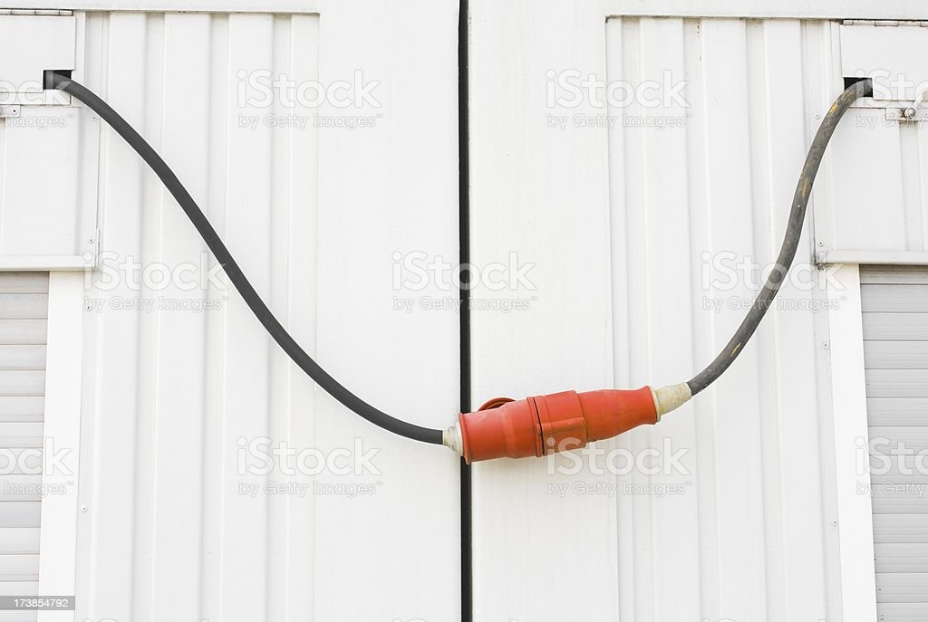 Strong red voltage connector against white siding stock photo