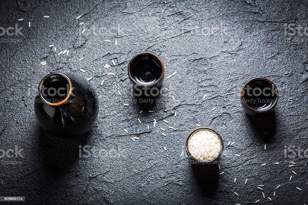 Strong sake in black ceramics on black rock stock photo