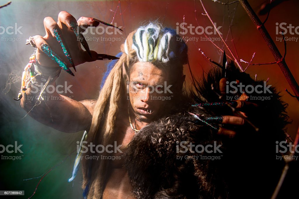 Strong scary werewolf with long nails in the wood stock photo