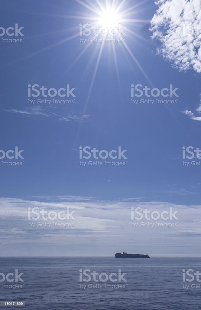 Strong Sun at Sea with Ship on the Horizon royalty-free stock photo