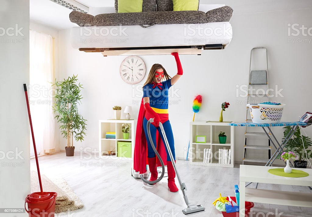 Strong super housewife cleaning home and holding bed stock photo
