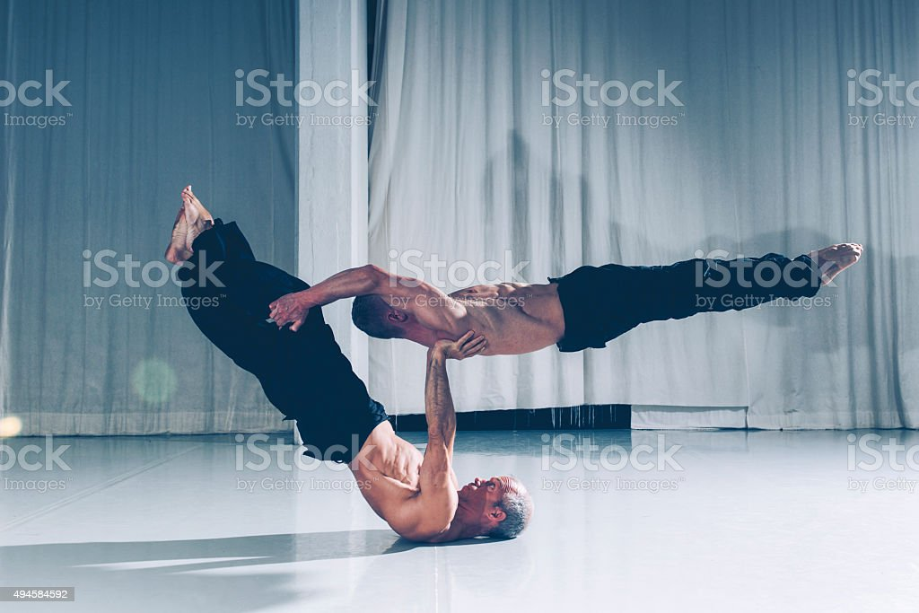 Strong teamwork with two acrobats supporting each other stock photo