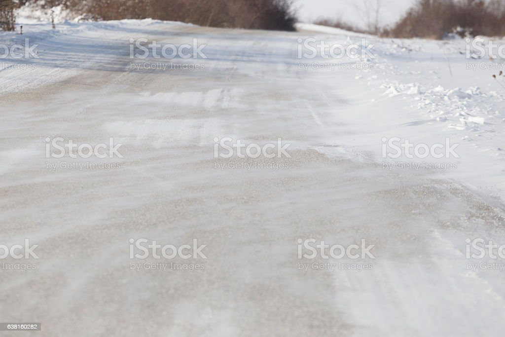 Strong wind drifts snow on asphalt road stock photo
