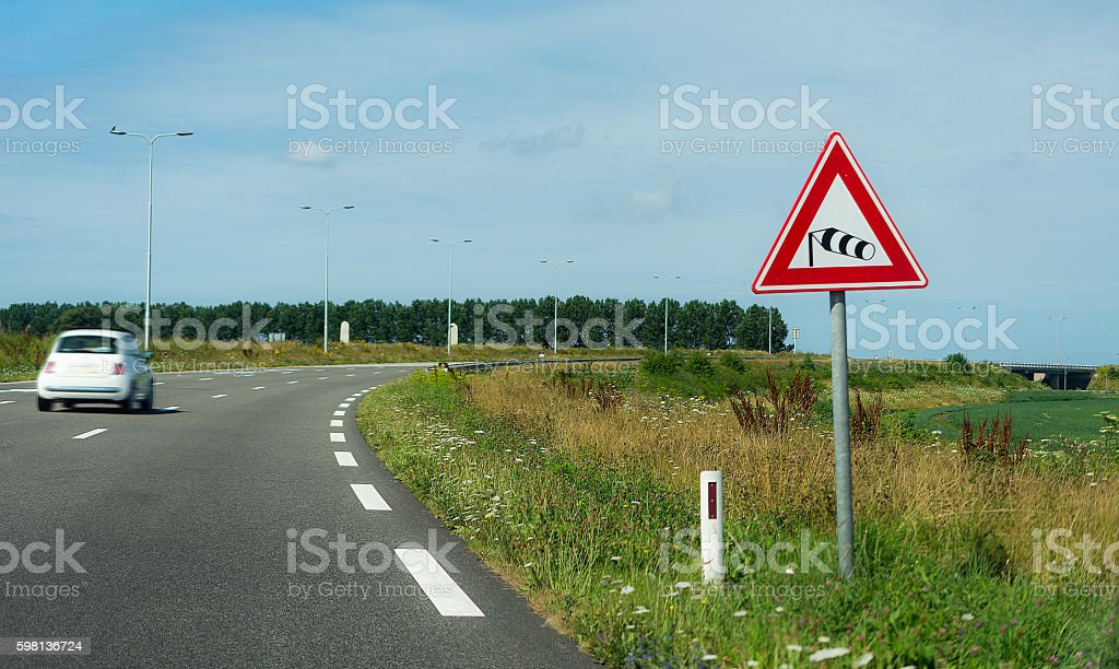 strong wind warning sign  in the side of the road stock photo