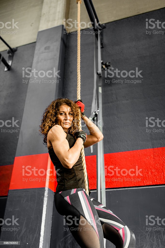 strong woman climbing the rope on a gym stock photo