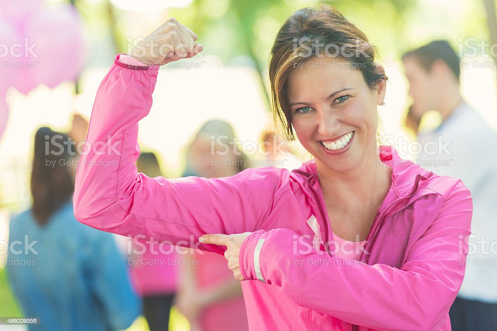 Strong woman showing muscles at charity breast cancer awareness event stock photo