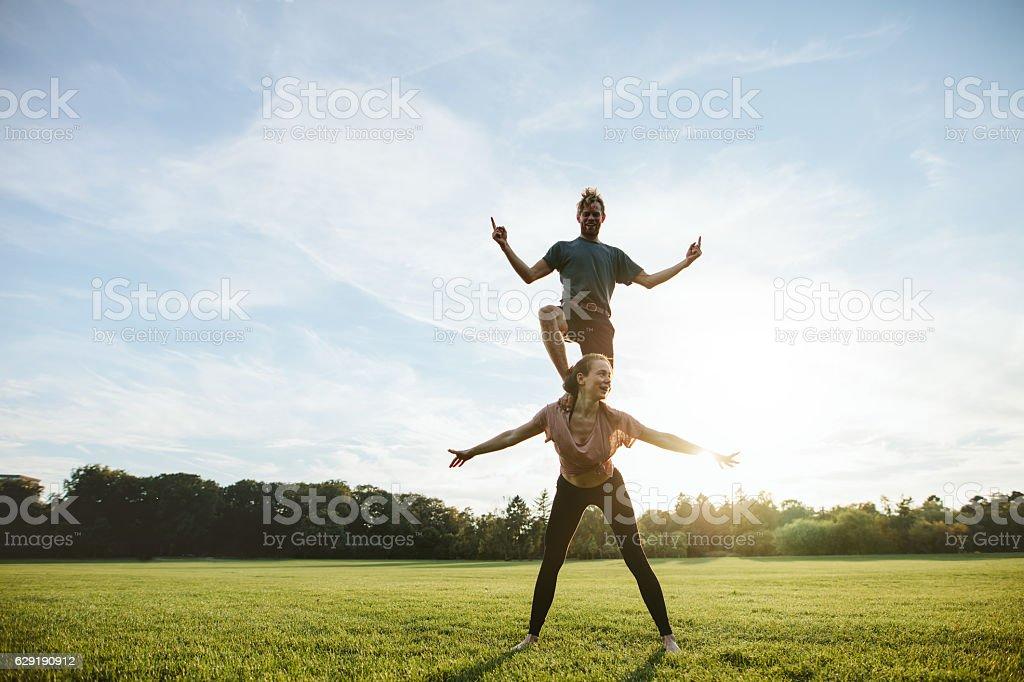 Strong young couple doing acrobatic yoga stock photo