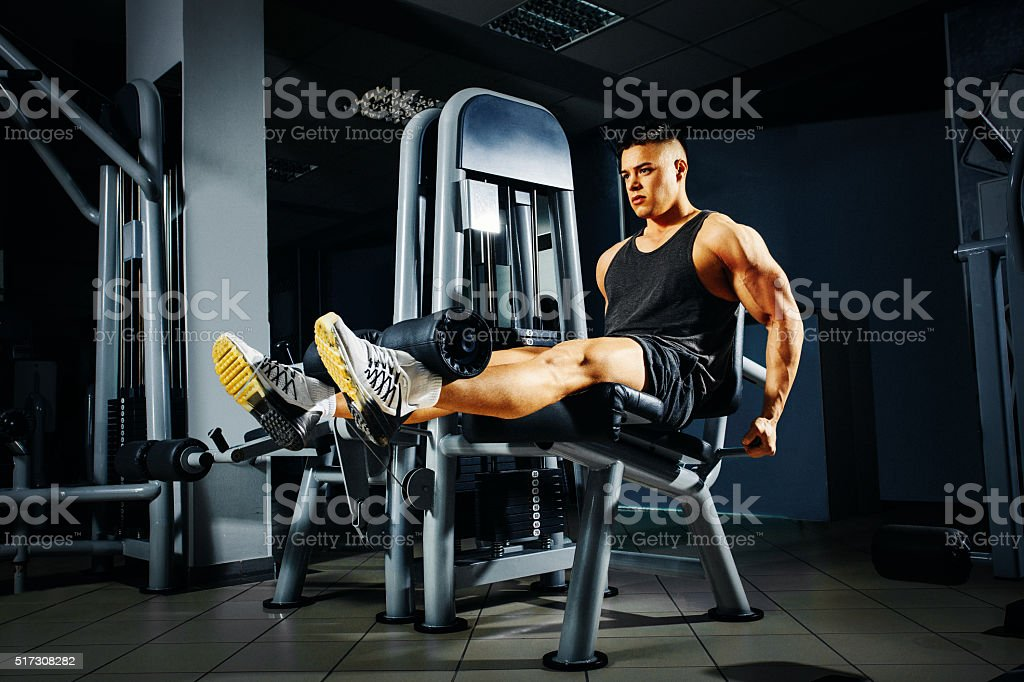 Strong young man doing legs exercise in the gym stock photo