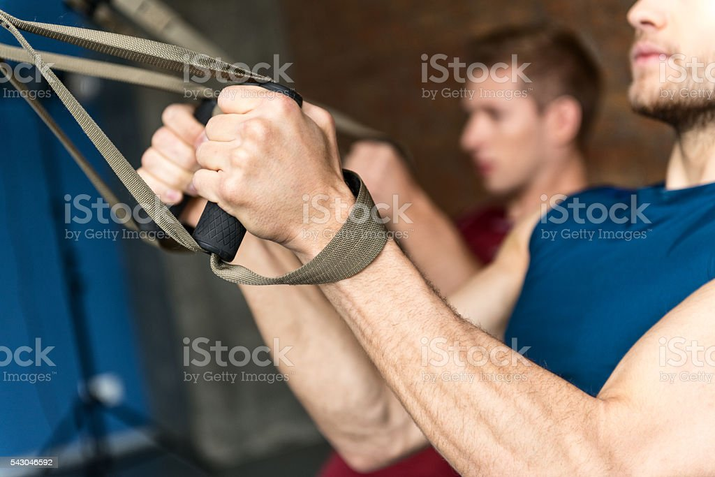 Strong young men training in gym stock photo