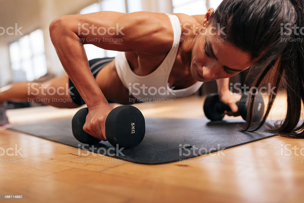 Strong young woman doing push ups stock photo