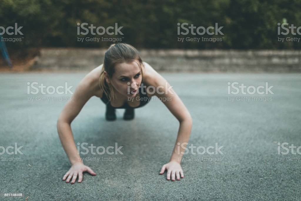 Strong young woman doing push-ups stock photo