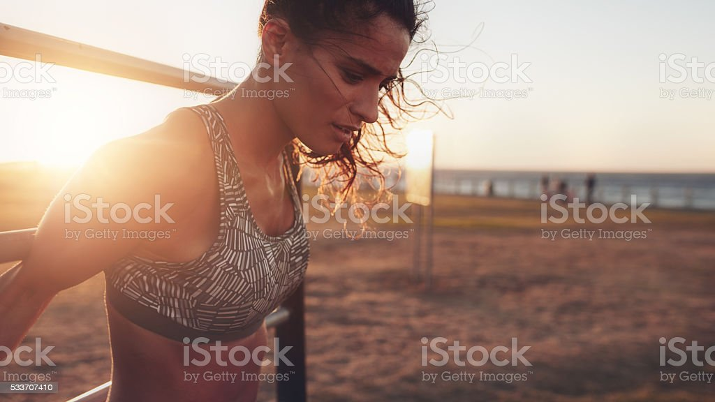 Strong young woman exercising on wall bars stock photo