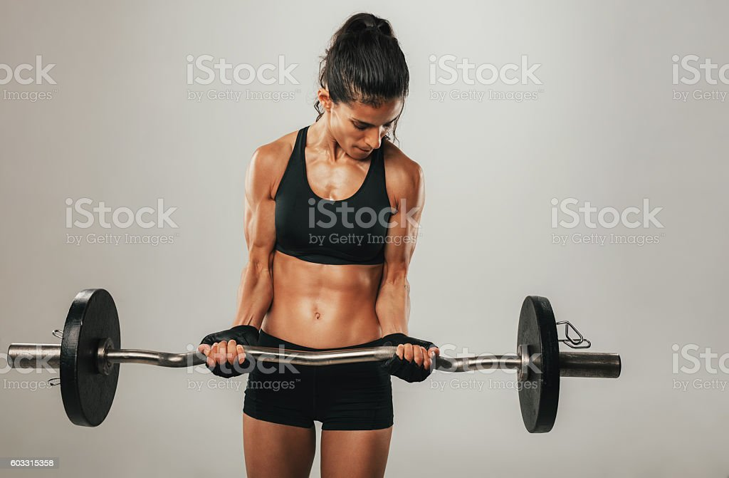 Strong young woman lifting barbell stock photo