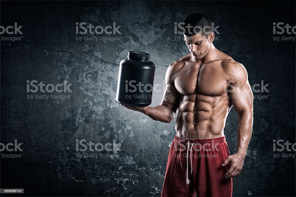 Strongman with can of supplements stock photo