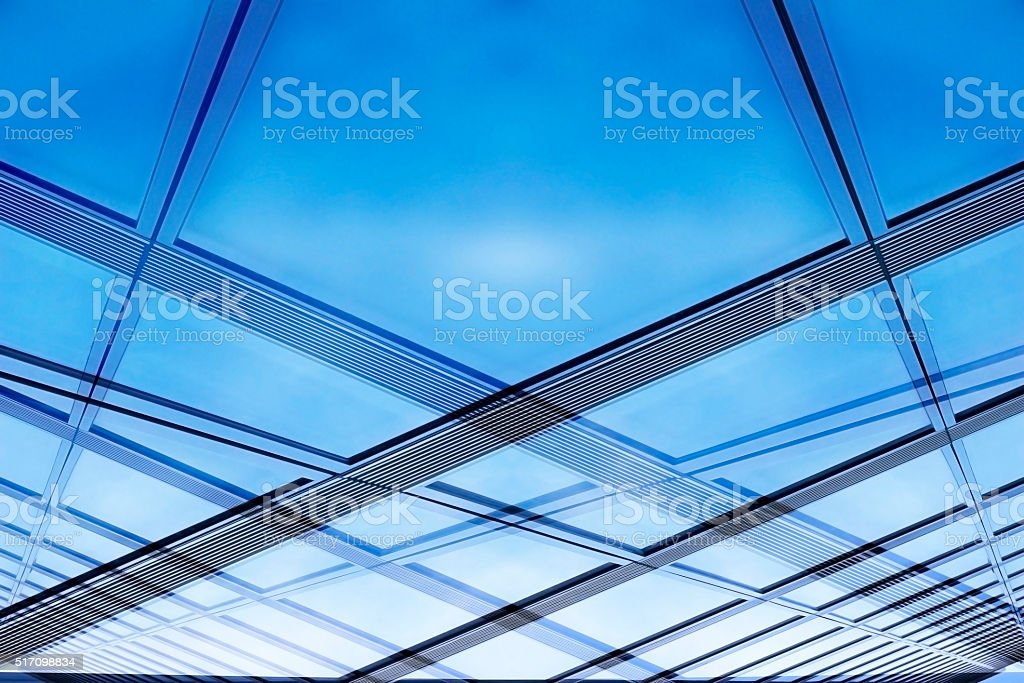 Structural glass wall / ceiling reflecting bright sky stock photo