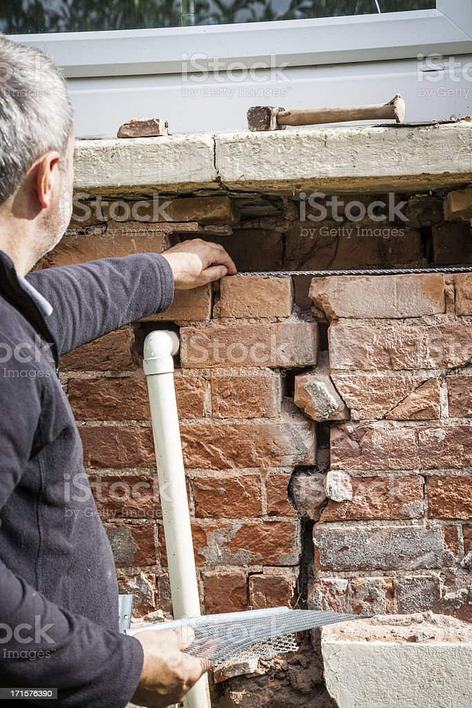 Structural problem: Repairing a cracked wall royalty-free stock photo
