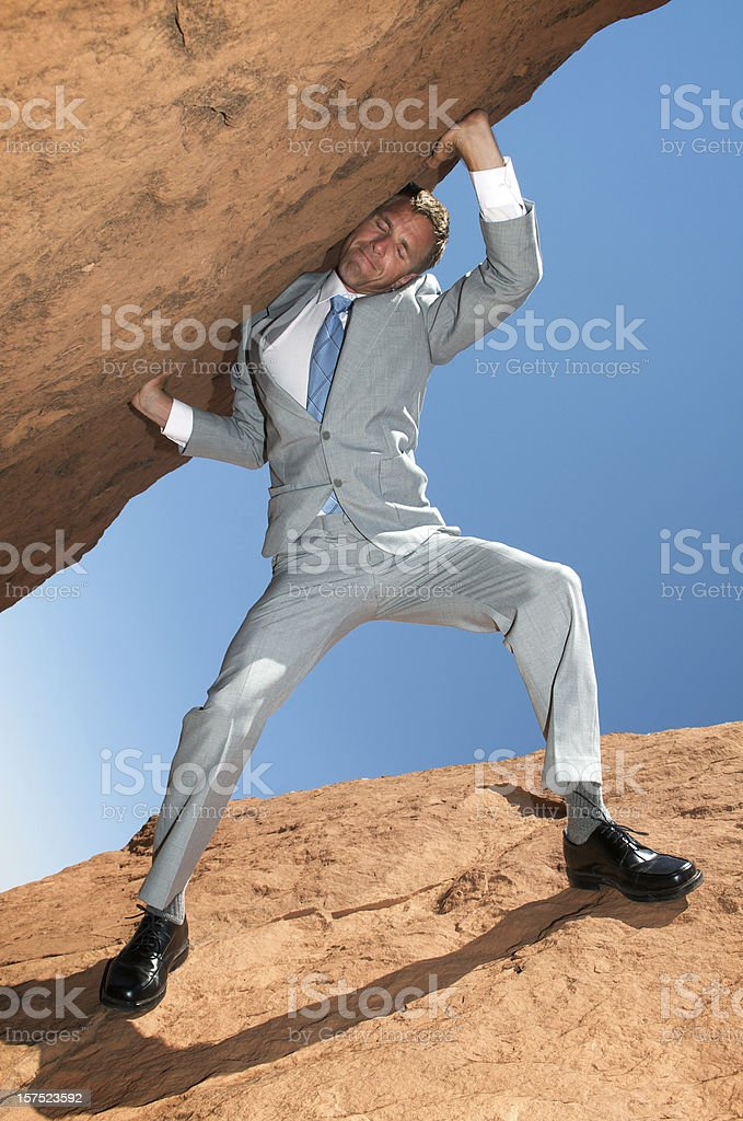 Struggling Businessman Carrying Huge Rock Into Sky royalty-free stock photo