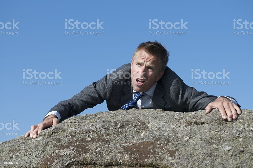 Struggling Businessman Climbing to the Top of a Rock royalty-free stock photo