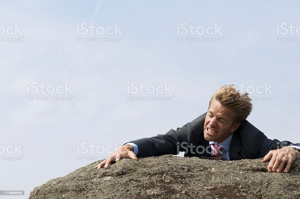 Struggling Businessman Clinging to Edge of Windblown Rock royalty-free stock photo