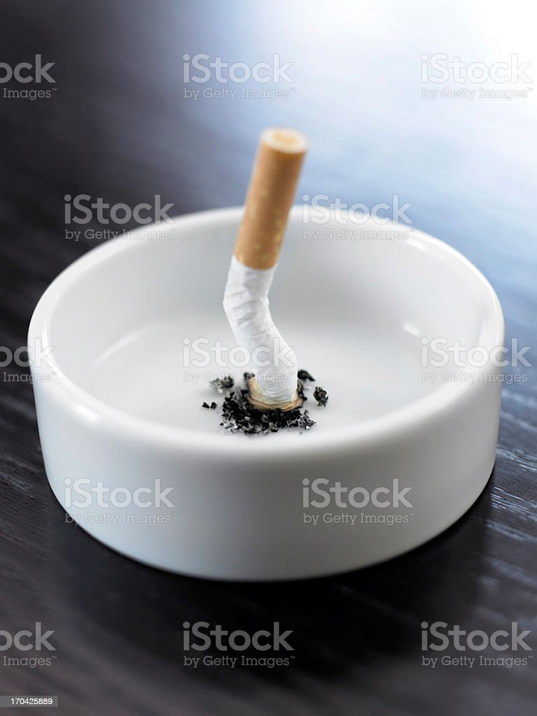 Stubbed out cigarette in ashtray stock photo