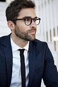 Stubble businessman in glasses, close up