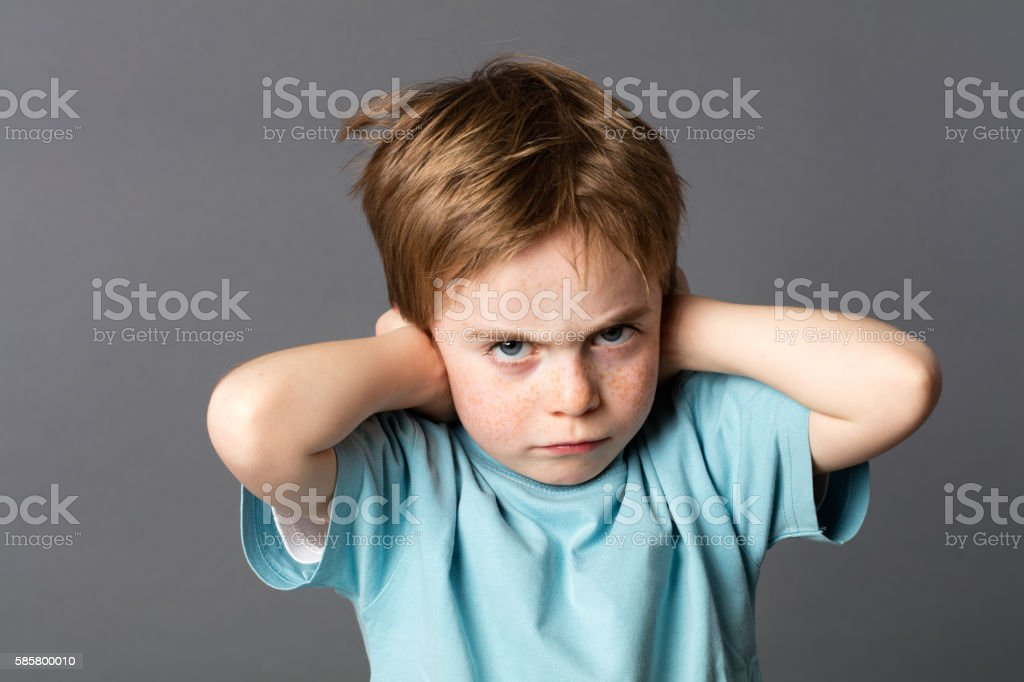 stubborn kid with an attitude ignoring parents scolding, blocking ears stock photo