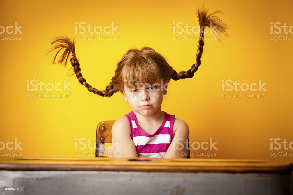 Stubborn Red-Haired Girl with Upward Braids in School Desk stock photo