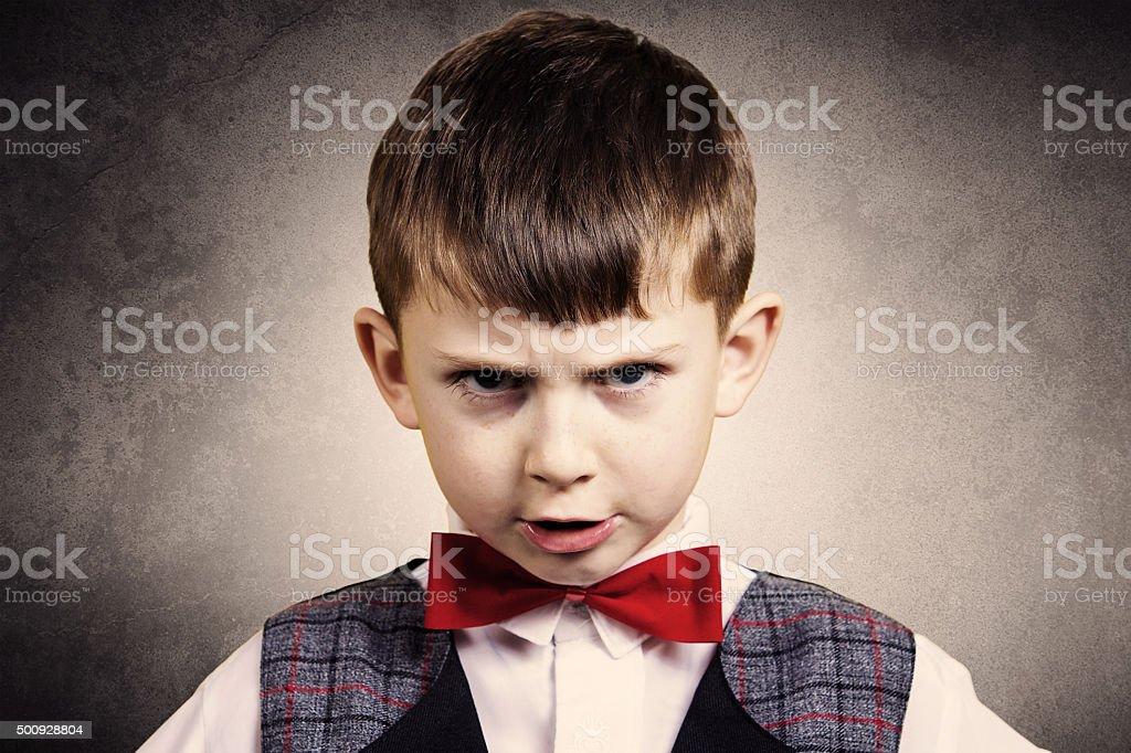 Stubborn,sad,upset  little boy,child  isolated over grey backgro stock photo