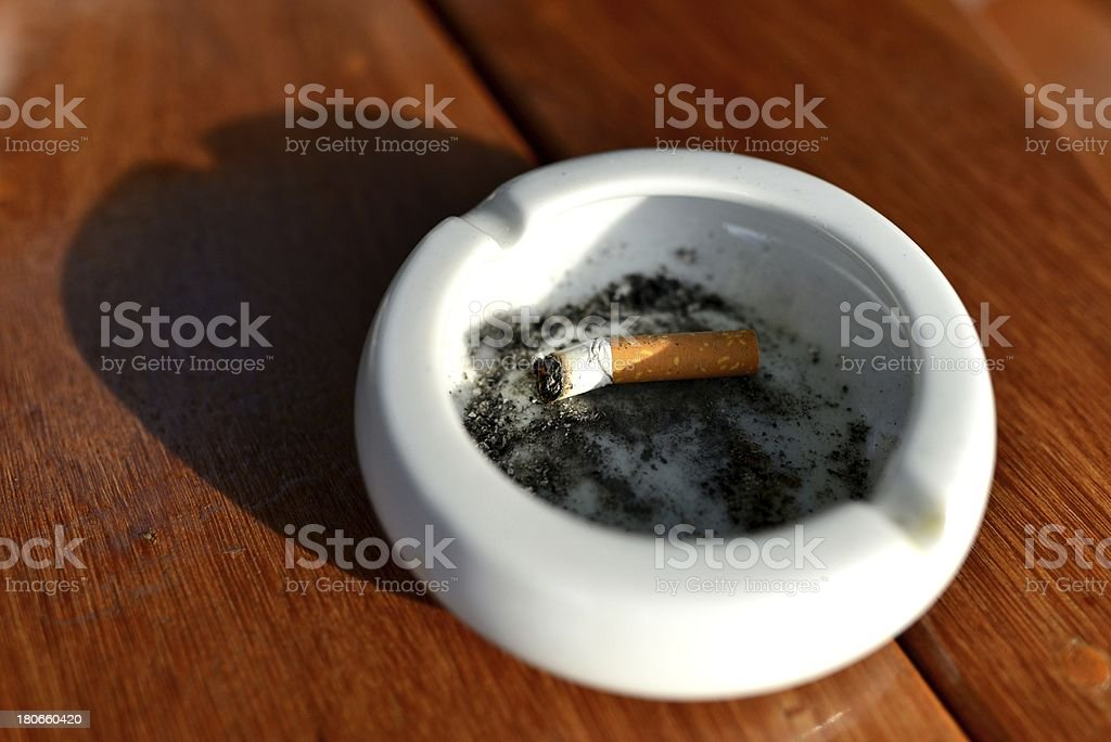 stubs of cigarette  in white ashtray on the table royalty-free stock photo