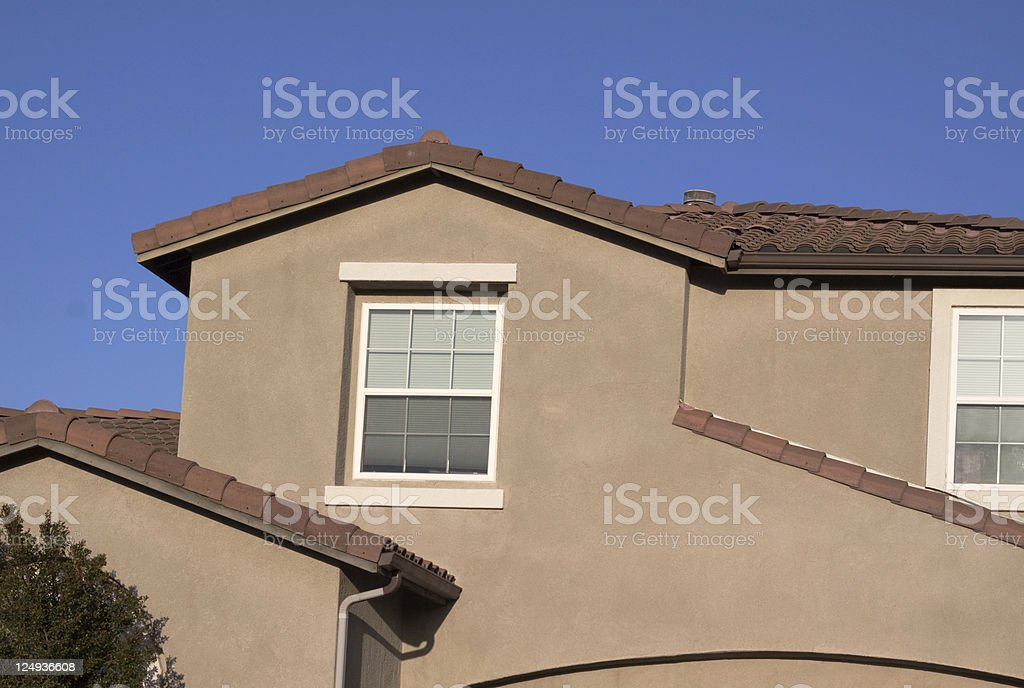 Stucco Home Exterior and Blue Sky stock photo