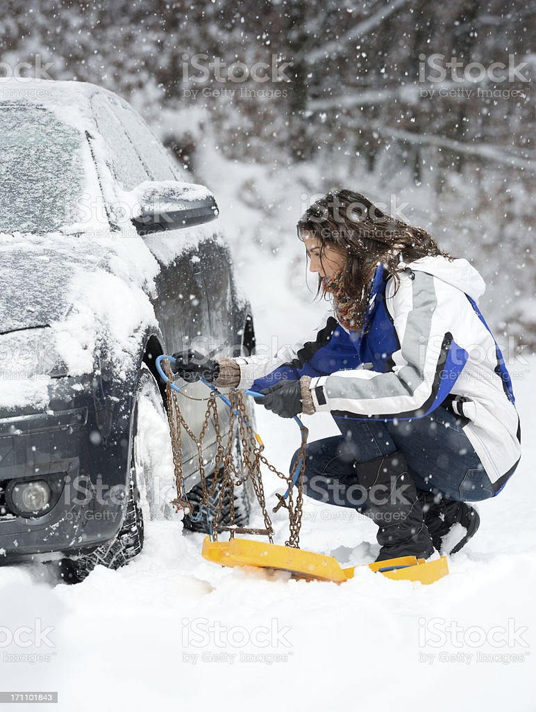 Stuck in a Blizzard, Woman applying Snow Chains stock photo