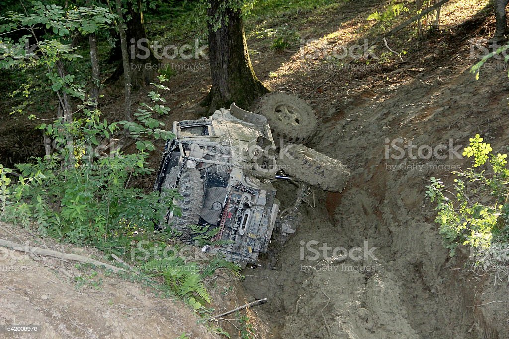 Stuck Offroad vehicle scaling uphill through mud with car winch stock photo