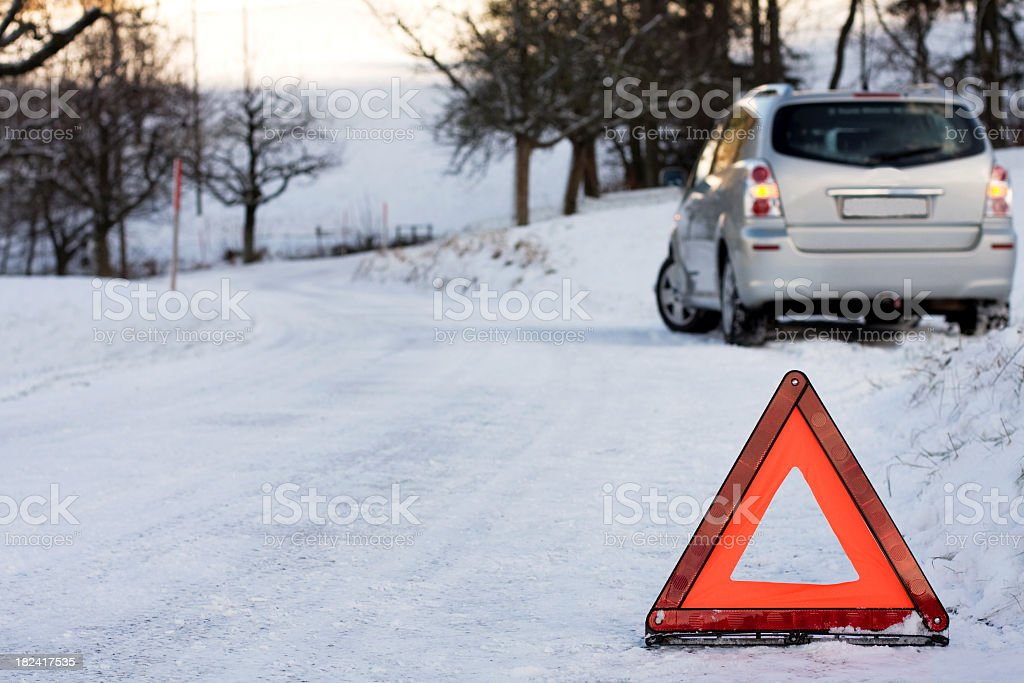 SUV stuck on a snowy road, protected by a hazard sign royalty-free stock photo