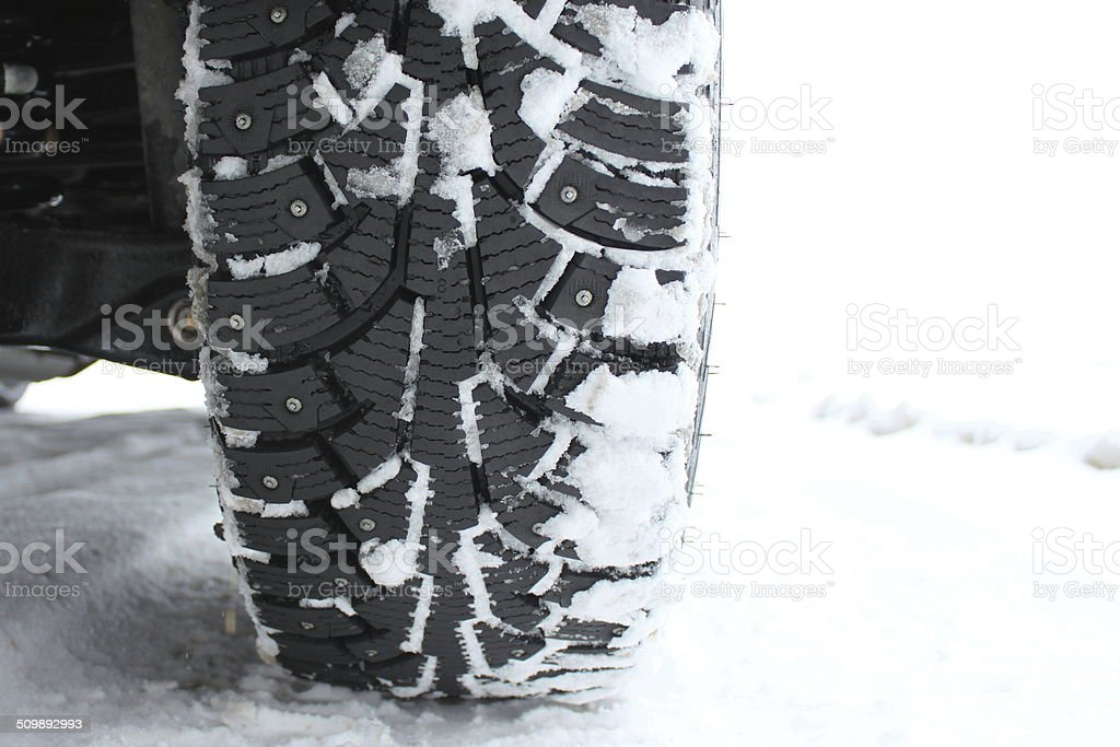 Studded snow tire in the winter close-up stock photo