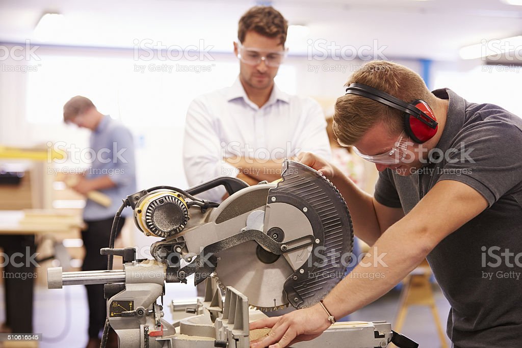 Student And Teacher In Carpentry Class Using Circular Saw stock photo