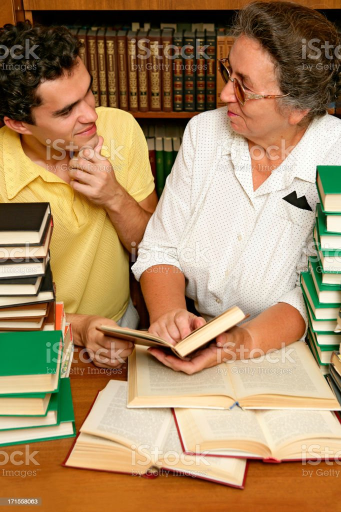 Student and teacher with lots of books stock photo