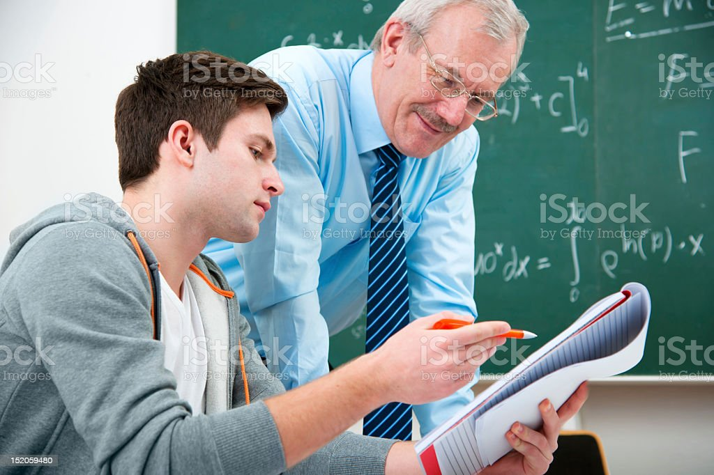 A student and teacher working together in a classroom  stock photo