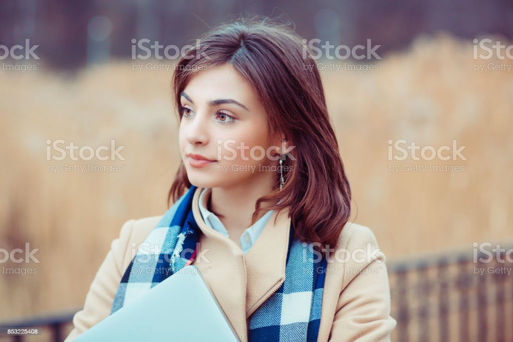 Student, business woman looking away. Closeup portrait professional beautiful confident young girl holding books isolated park cityscape outdoor background. Multicultural mixt race asian russian model stock photo