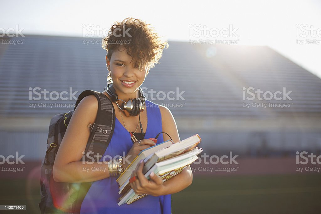Student carrying books on football field royalty-free stock photo