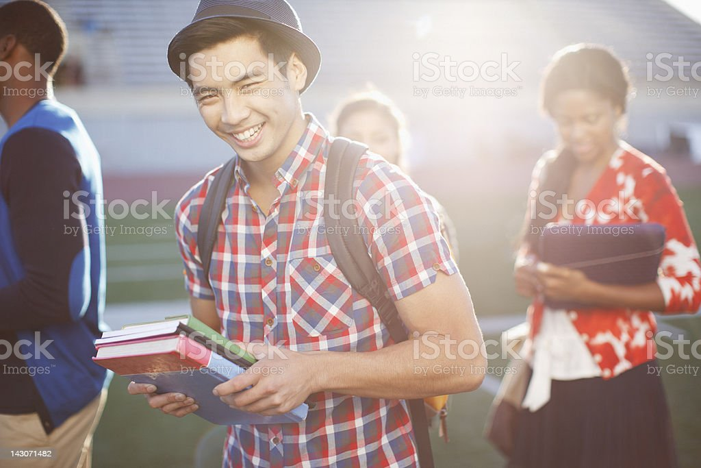 Student carrying books outdoors stock photo