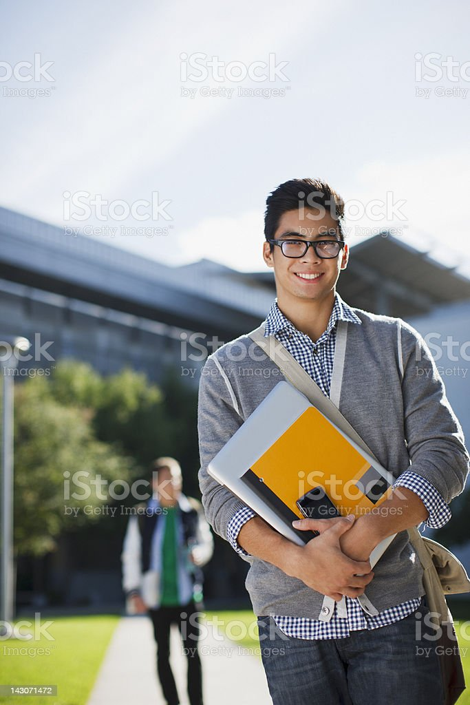Student carrying folders outdoors stock photo