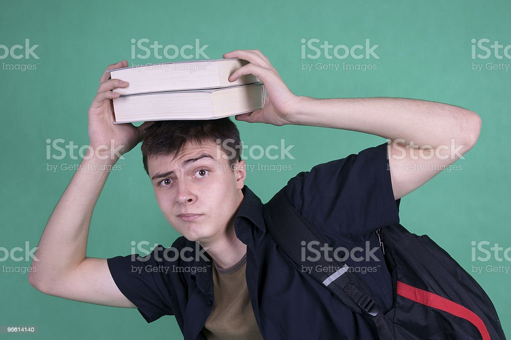 Student carrying heavy books on his head royalty-free stock photo