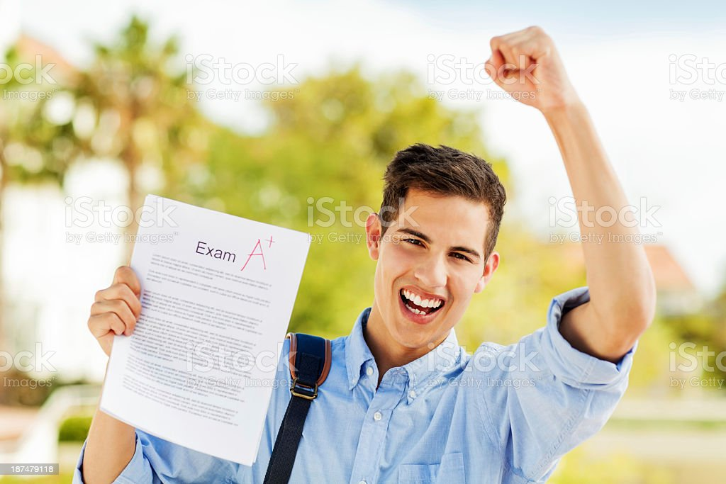 Student Clenching Fist While Holding Exam Paper With A+ Grade royalty-free stock photo