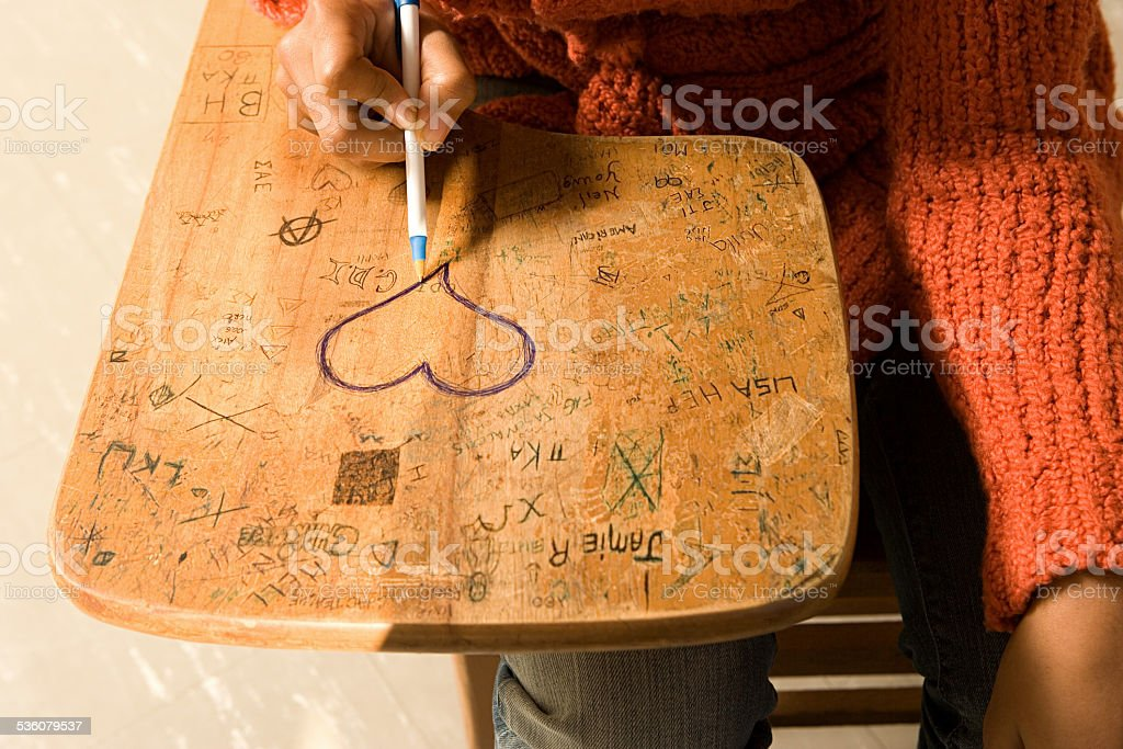 Student drawing a heart on her desk stock photo