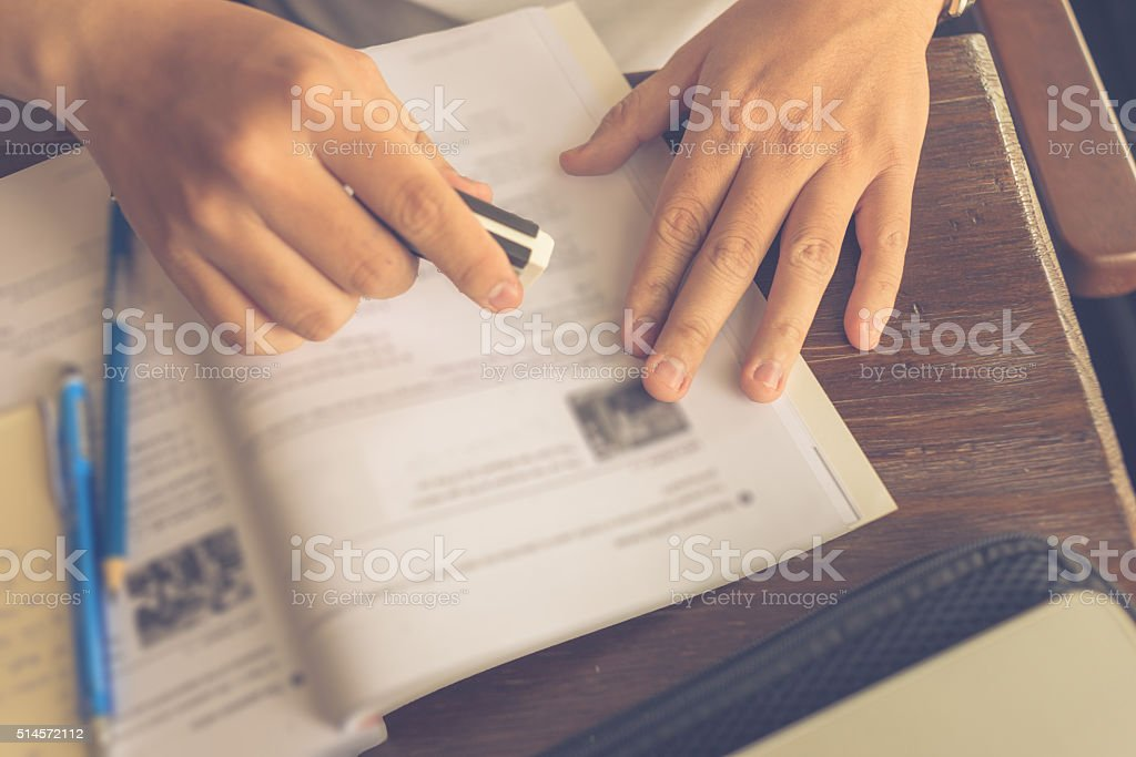 Student erasing wrong mistake with the eraser stock photo