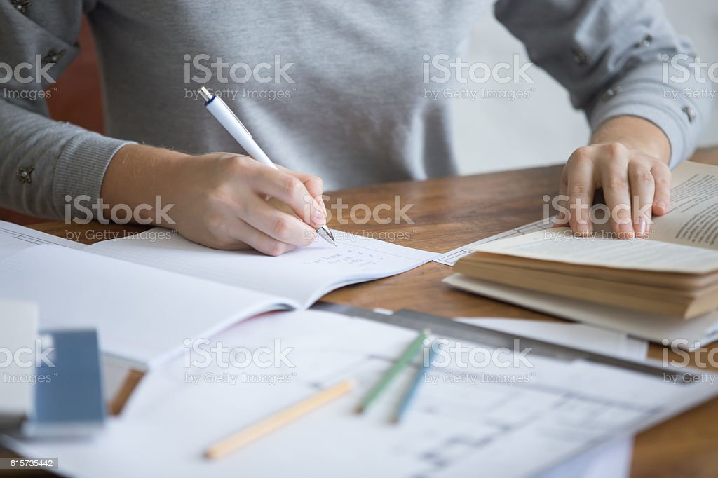 Student female hands performing a written task in a copybook stock photo