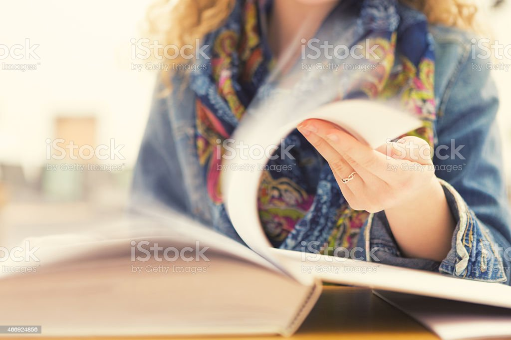 Student flipping through book; motion of turning pages stock photo