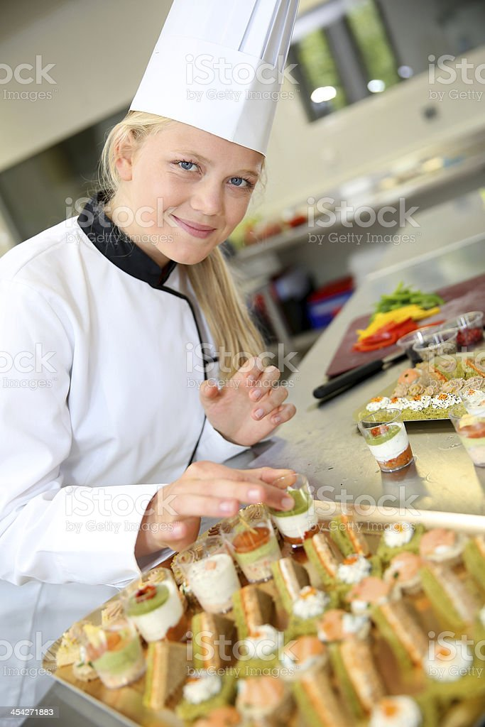 Student girl finishing a tray of appetizers stock photo