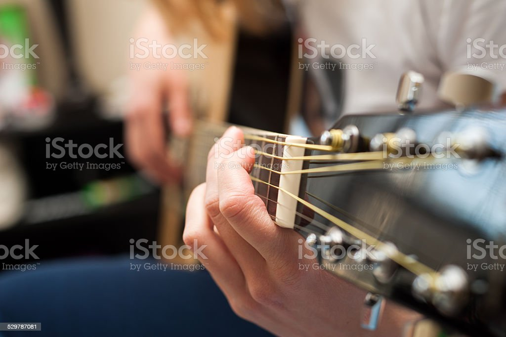 Student girl playing the guitar close-up with focus on hand stock photo